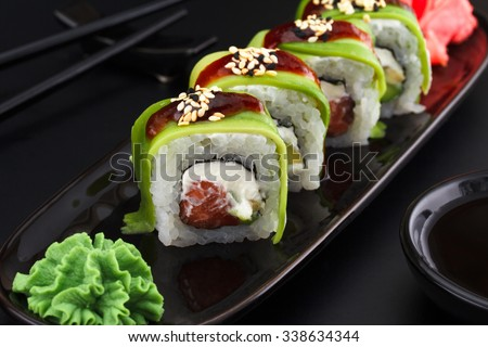 Premium quality sushi rolls with ginger wasabi and soy sauce over black background - stock photo