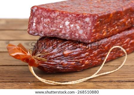Premium salami, cut on wood grain surface. - stock photo