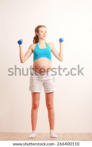 Prenatal exercises. Beautiful pregnant woman exercising with dumbbells - stock photo