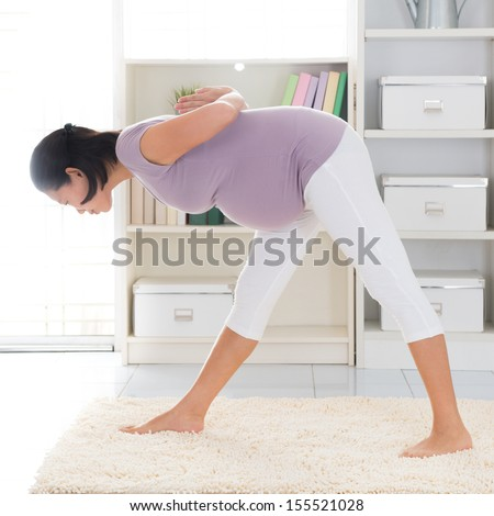 Prenatal yoga. Full length healthy 8 months pregnant calm Asian woman meditating or doing yoga exercise at home. Relaxation yoga forward bending pose. - stock photo