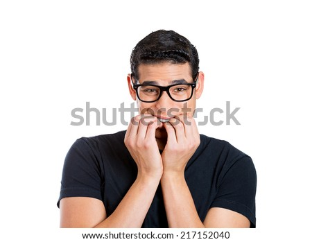 Preoccupied man. Anxious guy with glasses biting fingernails, feels insecure isolated white background. Human face expressions, emotions, body language, life perception  - stock photo