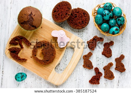 Preparation chocolate bunny for cute Easter cake. Cut rabbit of chocolate cupcakes on a festively decorated white table with colorful eggs - stock photo
