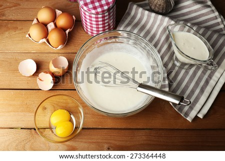 Preparation cream with eggs in glass bowl on wooden background - stock photo