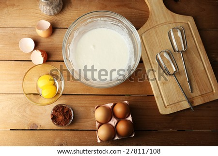 Preparation cream with eggs in glass bowl on wooden table, top view - stock photo