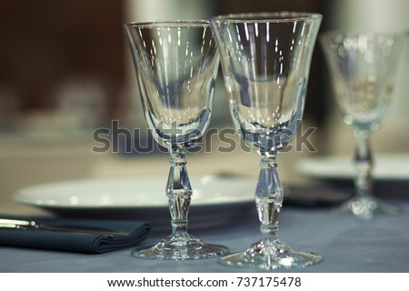 Preparation for a banquet. The tables are covered with lilac tablecloth. Wine glasses are on the tables in the restaurant.