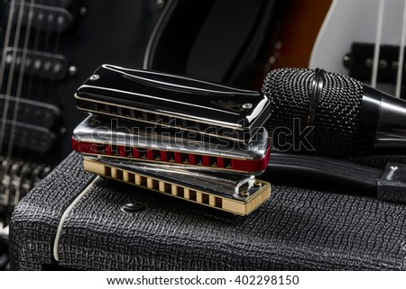 Preparation for a concert by getting ready the musical instruments. Harmonicas in a vertical row on the guitar amp. - stock photo