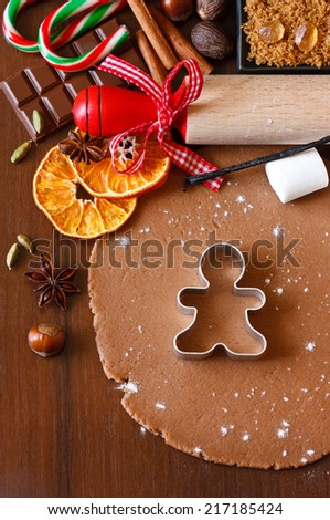 Preparation for baking Christmas cookies. Gingerbread dough with spices gingerbread man cookie cutter and rolling pin. - stock photo