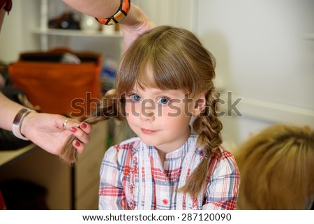 Preparation for children's photo shoot. Hairdresser makes hairstyle of two braids girl