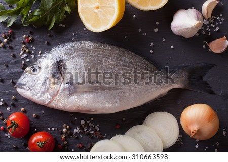 Preparation for cooking raw fish dorado with ingredients on a table close-up. Horizontal top view - stock photo