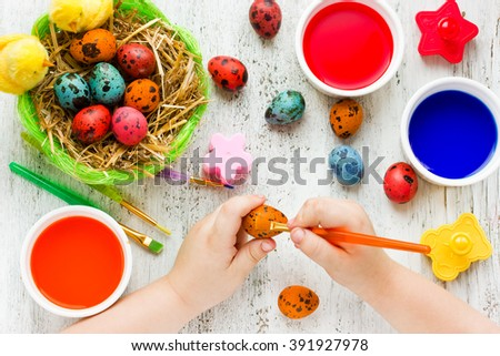 Preparation for happy Easter holiday. Child hands painting decorative colorful eggs, handmade Easter craft top view - stock photo