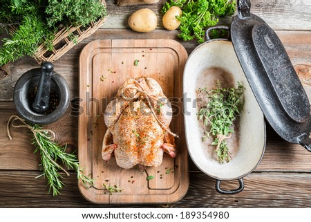 Preparation for roasting chicken with herbs - stock photo