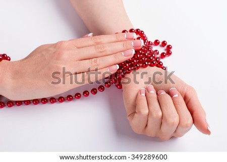 Preparation for the holiday. Red bracelets with beads on the female hands. Beautiful french manicure. Beauty style. - stock photo
