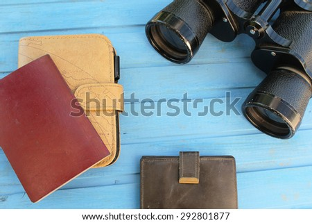 Preparation for travel - binoculars, passport, wallet and notebook - on blue wooden table with place for text in the middle - vintage style