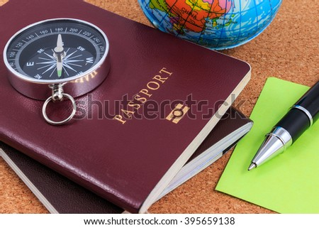Preparation for travel, compass, passport, pen and inflatable world globe on wooden table.