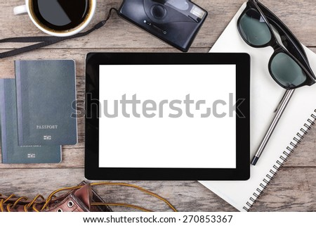 Preparation for travel,outfit, tablet ,passport, camera on wooden table