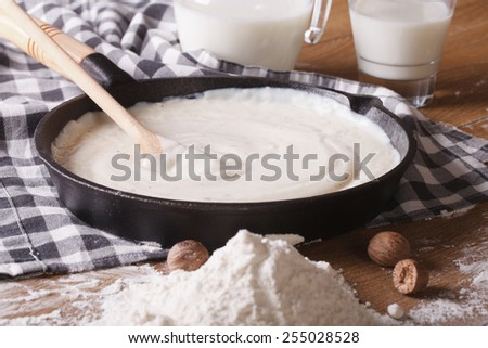 preparation of bechamel sauce in a pan and flour, milk on the table. horizontal