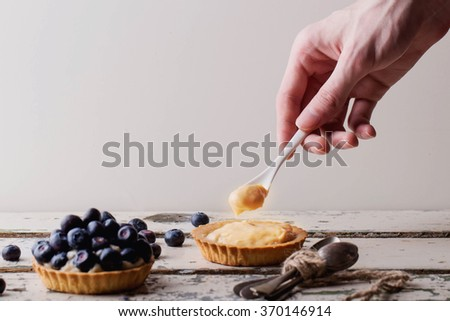Preparation of berry mini tarts with male hands, decorating the pastry with blueberries, over a rustic white wooden board - stock photo