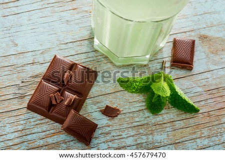 Preparation of delicious mint milkshake with green apples and ice cream. Chocolate pieces and mint leaves near the glass for decoration and amazing taste. - stock photo