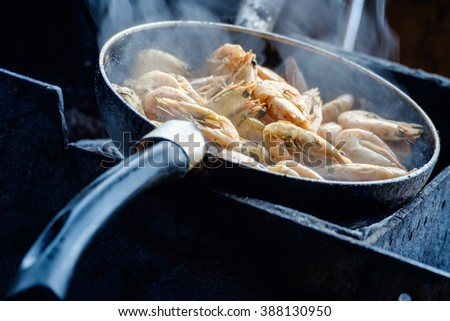 Preparation of delicious shrimp in the pan outdoors in the gazebo. - stock photo