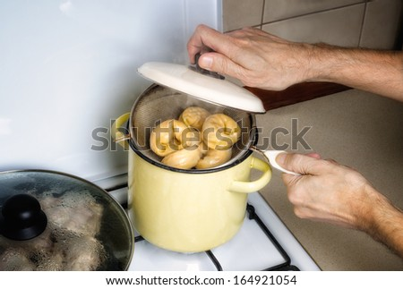 Preparation of delicious traditional steamed pelmeni in a yellow pot - stock photo