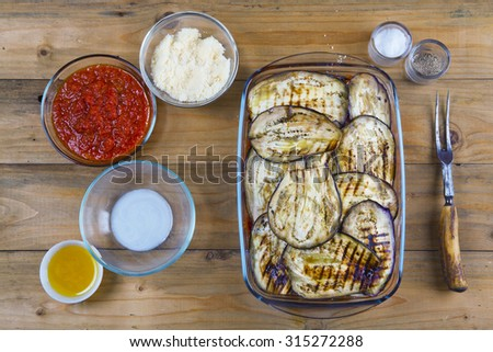 preparation of eggplant Parmesan. Italian vegetarian food. fried dish in the oven with cheese. typical traditional Mediterranean food - stock photo