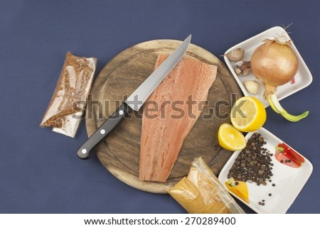 preparation of frozen salmon, salmon on a wooden chopping board - stock photo