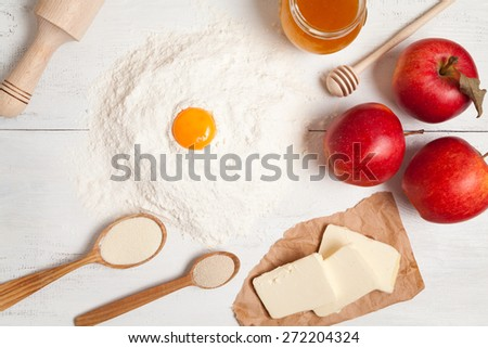 Preparation of fruit pie. Flour, butter, apples, honey and yeast on white rustic table - stock photo