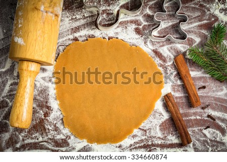 Preparation of gingerbread man cookies. Cookie dough, cookie cutters on parchment paper surrounded with christmas tree branch, spices and rolling pin. Flat lay, table top view food - stock photo