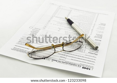 preparation of Internal Revenue Service form 1040 for income report and US tax return - stock photo