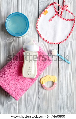 preparation of mixture baby feeding on wooden background top view