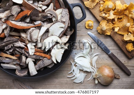 Preparation of mushrooms for frying: sliced leccinum on frying pan, chantarelles at cutting board.