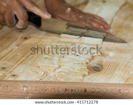 Preparation of Raw Homemade Italian Pasta on Wooden Cutting Board - stock photo