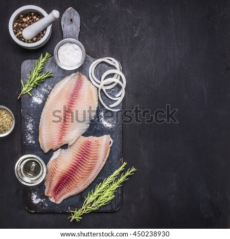 preparation of raw tilapia fillets with salt, oil and herbs, whole pepper in a mortar, laid out on a chopping board on a dark rustic background Border with space for text top view - stock photo