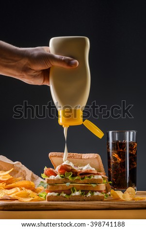 Preparation of sandwich with hand which is pouring mayonnaise on it. Lunch for everyone on a wooden desk with chips. Cold cola in glass with ice cubes. Unhealthy food. - stock photo