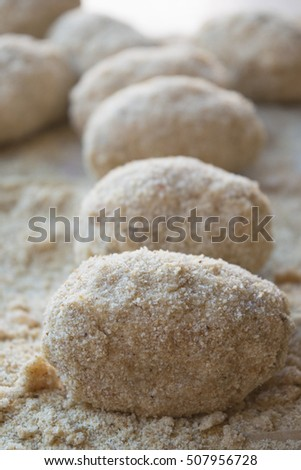 preparation of sicilian arancine with breadcrumbs on a paper