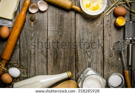 Preparation of the dough. Ingredients for the dough - milk, flour, eggs and different tools . On a wooden table.  Free space for text . Top view - stock photo