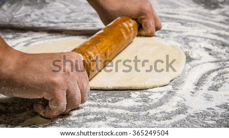 Preparation of the dough . The dough rolling the women's hands. On the stone table with flour. - stock photo