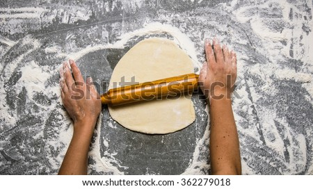 Preparation of the dough . The dough rolling the women's hands. On the stone table with flour. Top view - stock photo