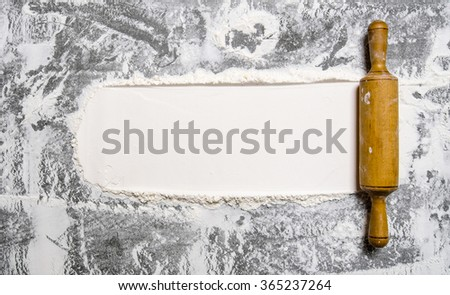 Preparation of the dough. The rolling pin with flour on a stone background. Free space for text. Top view - stock photo