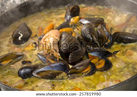 preparation of the valenciana paella with some of its traditional ingredients - stock photo