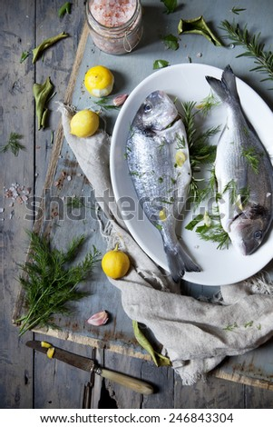 preparation of two fresh bream with herbal seasoning and lemon on rustic style table - stock photo
