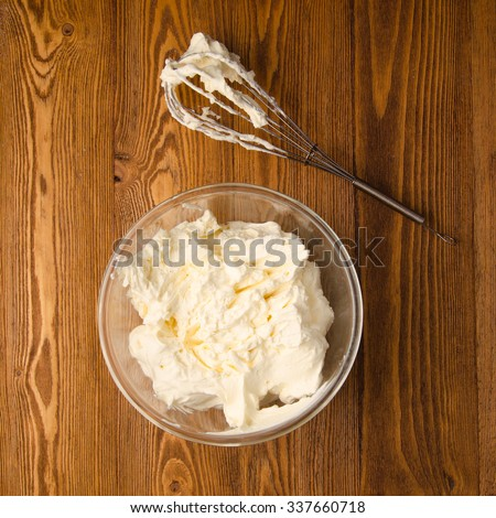 Preparation of whipped cream with a hand mixer metal on a wooden background. - stock photo