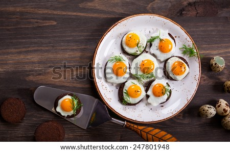 Preparation quail egg canapes with pumpernickel bread for Easter - stock photo