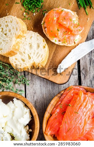 preparation sandwiches with smoked salmon: baguette with cream cheese, onion and cucumber - stock photo