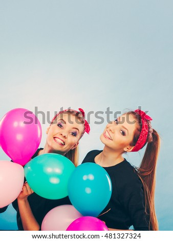 Preparation to birthday party. Two lovely happy retro girls preparing celebration. Smiling joyful women with multicolored balloons.