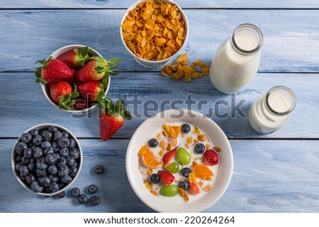 Preparations for breakfast corn flakes and fruits - stock photo
