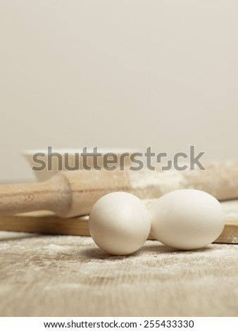Preparations for homemade baking. Basic ingredients for baking. Kitchen utensil with eggs rolling-pin wood spoon meal. Meal on table with cutting board. Flour. Baking. Egg - stock photo