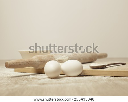 Preparations for homemade baking. Basic ingredients for baking. Kitchen utensil with eggs rolling-pin wood spoon meal. Meal on table with cutting board. Flour. Baking. Egg. Bake - stock photo