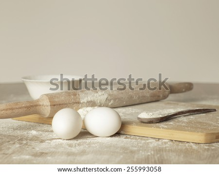 Preparations for homemade baking. Basic ingredients for baking. Kitchen utensil with eggs rolling-pin wood spoon meal. Meal on table with cutting board. Flour - stock photo