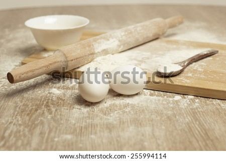 Preparations for homemade baking. Basic ingredients for baking. Kitchen utensil with eggs rolling-pin wood spoon meal. Meal on table with cutting board. Flour. baking - stock photo